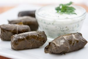 Dolma(tolma, sarma) in grape leaves with meat served with sauce from yogurt and greens.