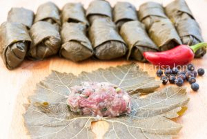 cooking of dolma from pickled grape leaves, minced meat and rice with jalapeno pepper on the wooden board close up