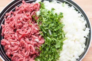 Raw minced meat with finely chopped fresh greens and onion in a bowl closeup.