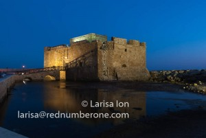 Illuminated Paphos Castle located in the city harbour at night with reflection in the water, Cyprus