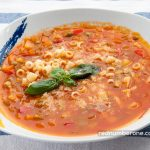 Minestrone soup with grated parmesan cheese and basil leaves