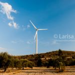 Wind turbines on the hill with olive trees, blue sky and clouds as a background. Eco power.