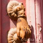 Hand-shaped door knocker on wooden door close up. Lefkara. Cyprus.