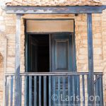 Old blue wooden balcony with blue door on the facade of one house. Lefkara. Cyprus.