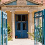 View of the Facade of High School Building thru open gates. Lefkara. Cyprus.