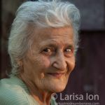 Outdoor portrait of an smiling old woman with flares of sun on her face. Closeup.