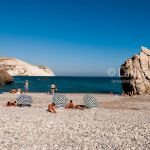 Tourists walking and swimming on the Aphrodite beach. Aphrodite's rock and Petra Tou Romiou famous landmarks of Cyprus.