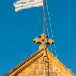 Greek flag on the roof of old church with the blue sky as a background.